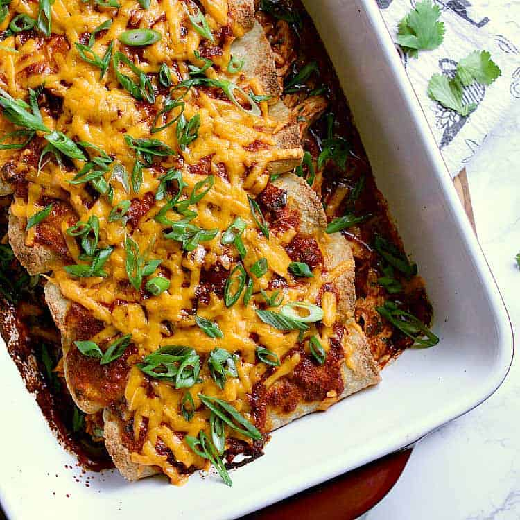 Baking dish with 8 keto enchiladas, covered in melted cheese and green onion.