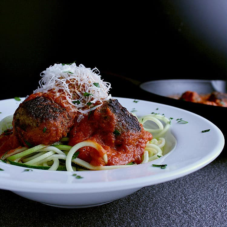 Plate with zoodles, keto meatballs and fresh parmesan cheese.