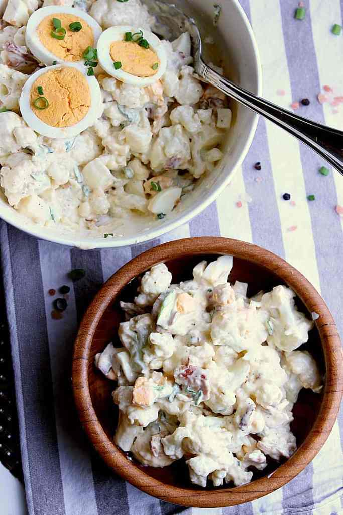 Mixing bowl of cauliflower potato salad next to a small wooden bowl of salad.