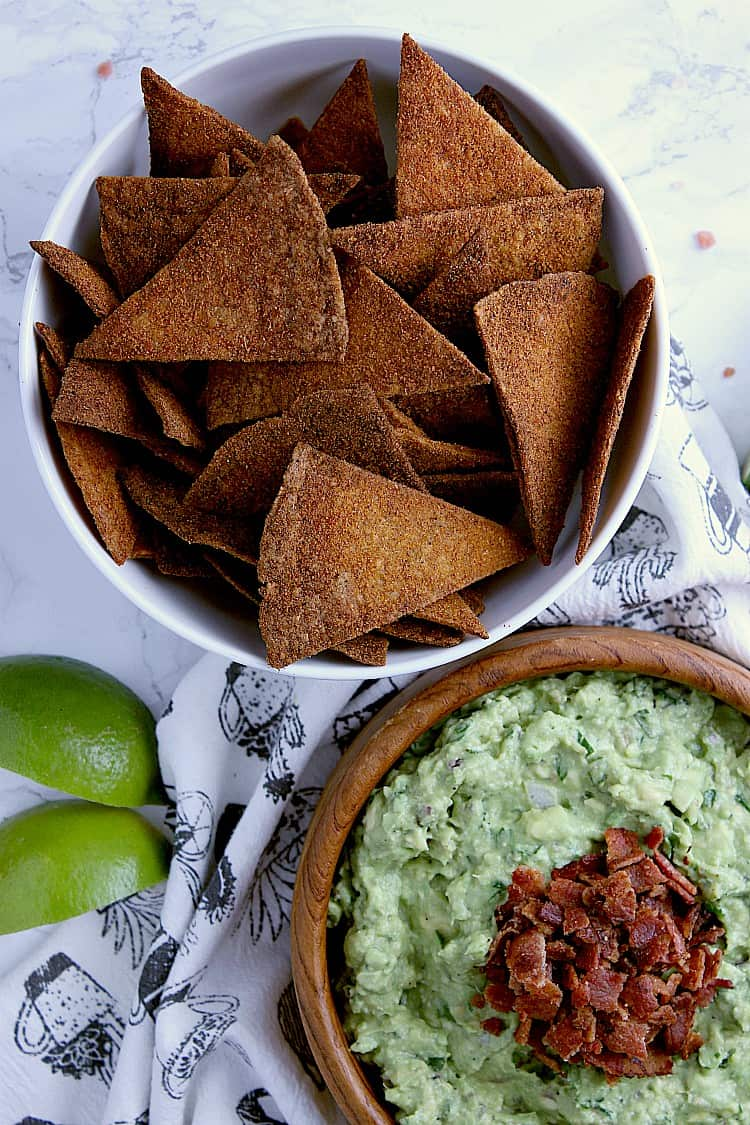 Bowl of nacho keto chips next to a bowl of keto guacamole.