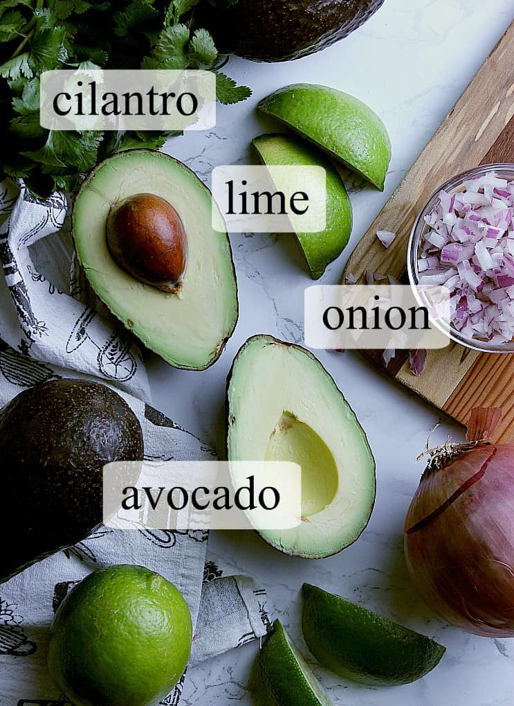 Pictured are the staple ingredients to make a keto guacamole: avocado, lime, onion and cilantro.