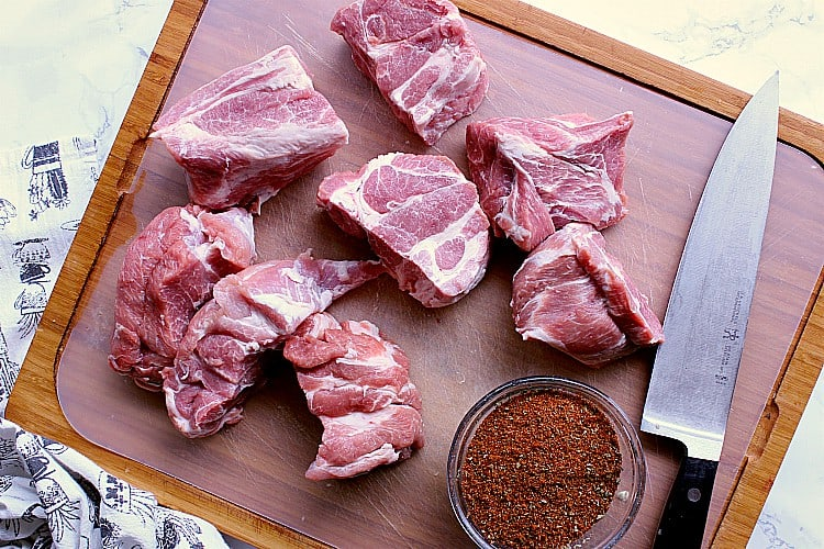Cutting board with pork chopped into 8 pieces. There is a knife on the cutting board along with the mixed rub.