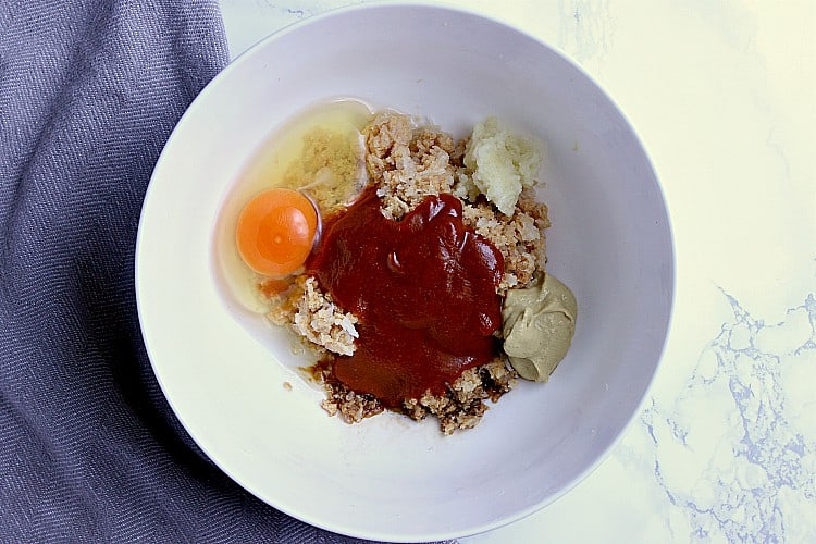 Bowl with crushed pork rinds, grated onion, bbq sauce, dijon, garlic, egg and worcestershire.