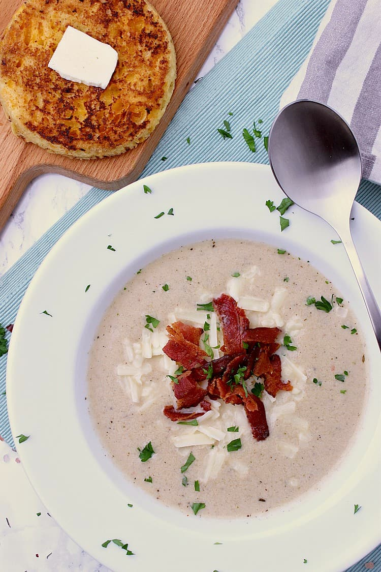 White bowl filled with Keto Cauliflower Soup and garnished with grated cheddar, crisp, crumbled bacon and minced parsley. A spoon is on the side of the bowl and some bread behind.
