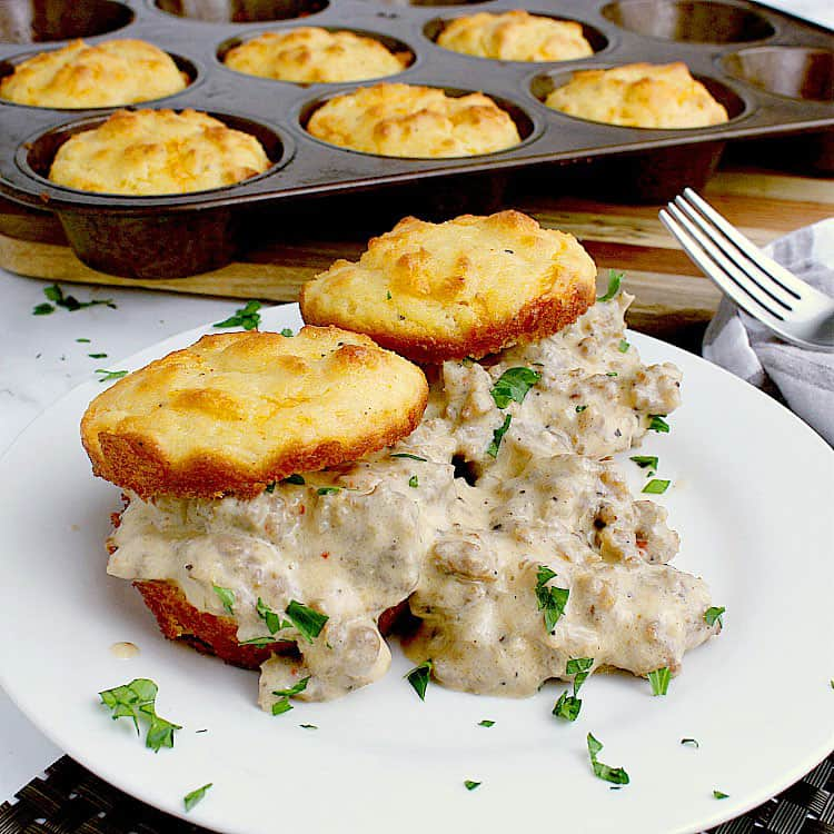 A plate with two biscuits, each cut in half and loaded with sausage gravy. The remaining tray of biscuits are behind the plate.