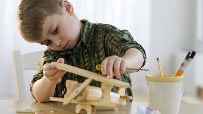 menino brincando com aviao de madeira