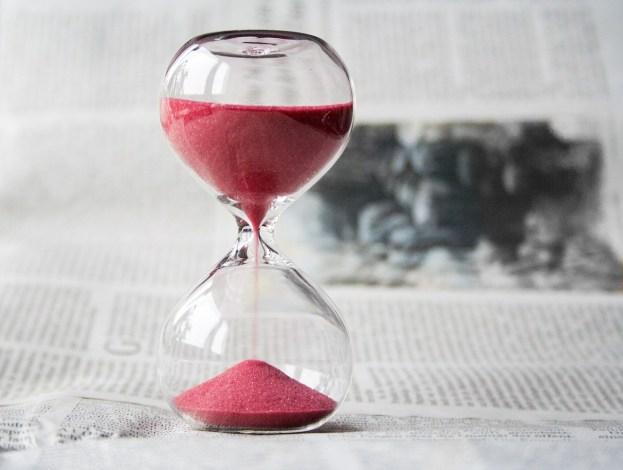 Sanduhr mit rotem Sand als Sinnbild dafür, wie die Zeit verrinnt