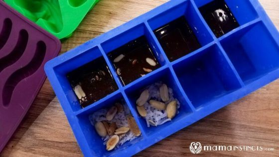 Blue silicone mold in square shape with coconut oil and chocolate mixture to make chocolate coconut bars.