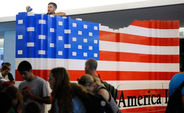 LEGO master builder Chris Steininger places a brick while building the world's largest LEGO American flag to celebrate the opening of the Innovation Wing at the National Museum of American History on Wednesday, July 1, 2015 in Washington.