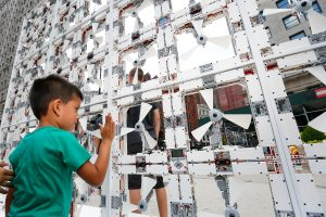 A young New Yorker investigates how he can cool down in front of a fully-functioning Wall of Fans made from LEGO® Technic elements, standing 8 feet tall and 12 feet long, during its temporary installation in the Flatiron District on Wednesday, August 5, 2015 in New York. (Mark Von Holden/AP Images for Lego Group)