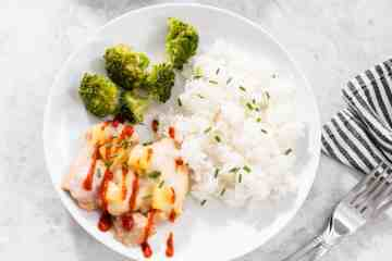 pineapple baked chicken drizzled with sriracha with white rice and broccoli on white plate