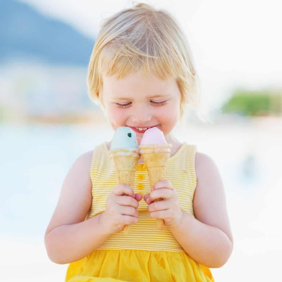 toddler girl in yellow dress with ice cream cones