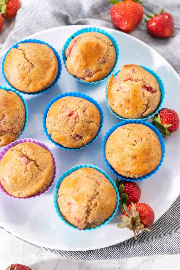 healthy strawberry muffins in colorful blue and purple silicone muffin liners with fresh strawberries on white plate