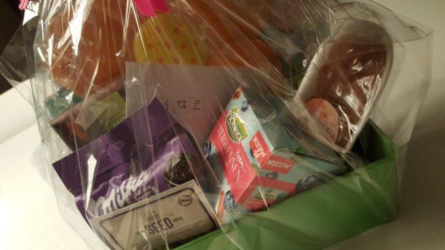 Bloembak met zaadjes, gedroogde abrikoos, thee, koekjes, chocolade en een voorleesboek