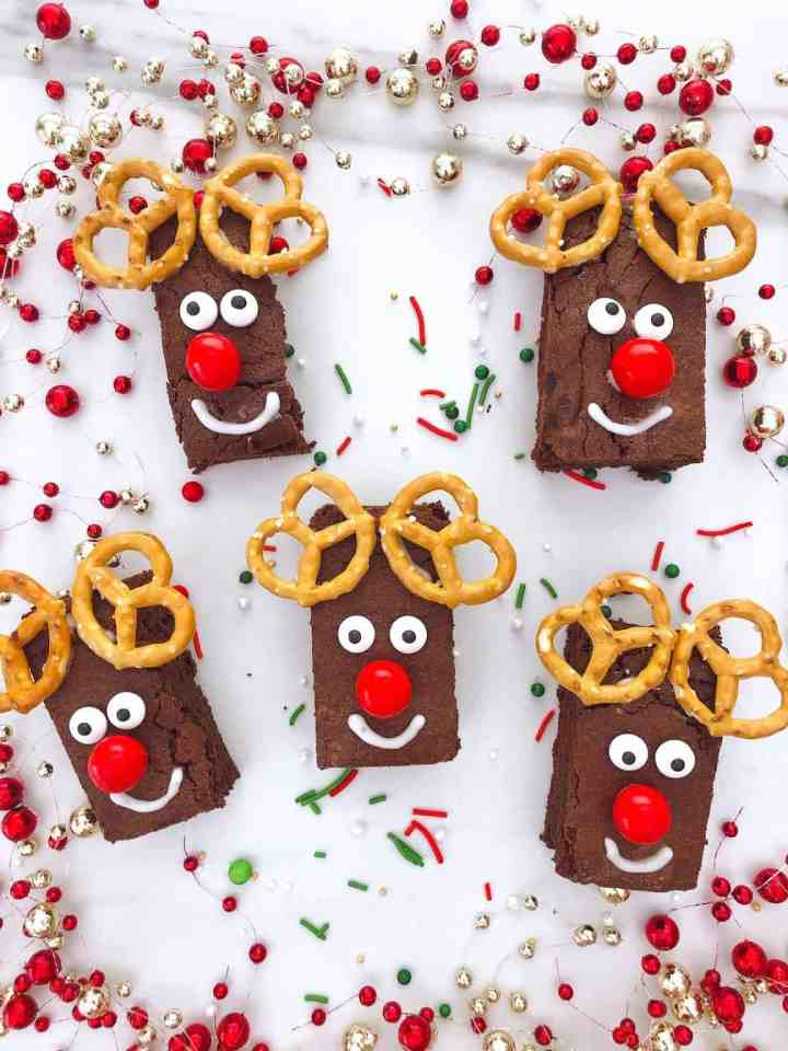 creative dessert Christmas recipe with cute reindeer shape of brownies made from pretzel and m&m