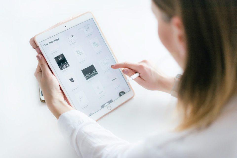 femme tenant une tablette et lit un article de blog