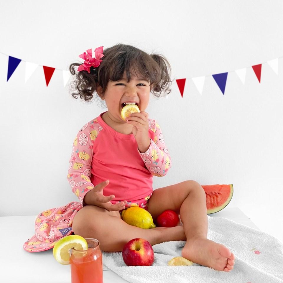 bebe fille qui porte un maillot de bain anti-uv fête 14 juillet pasteque citron jus de fruit
