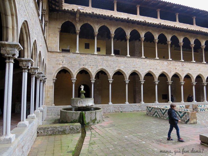 Niño en el claustro del Real Monestir de Santa Maria de Pedralbes, al lado de una fuente