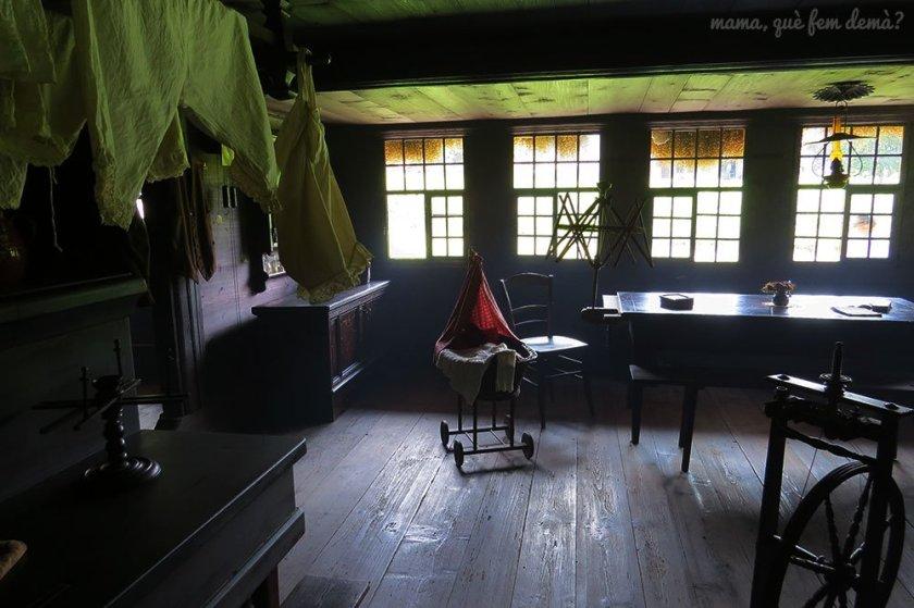 Interior de una casa en el Museu Ballenberg. Es un comedor con una cuna y ropa tendida