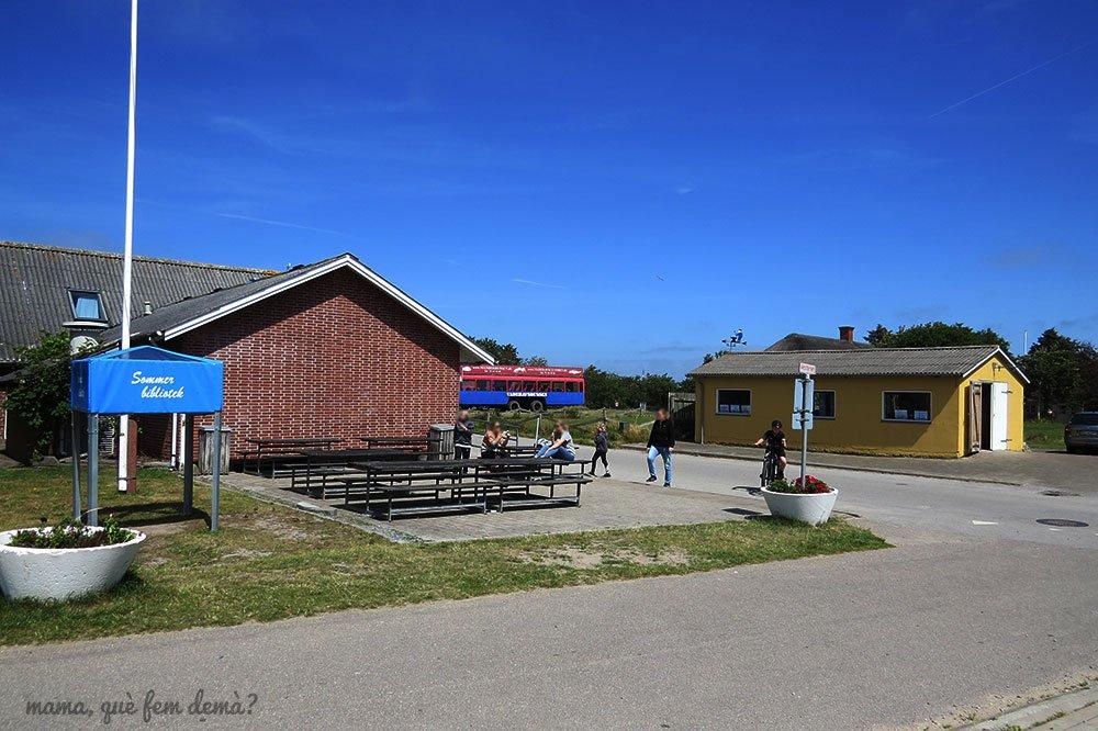 Supermercado, mesas de picnic y mini biblioteca en Mando