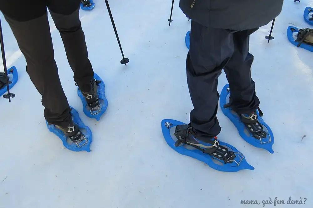 Piernas y pies que llevan raquetas de nieve azules