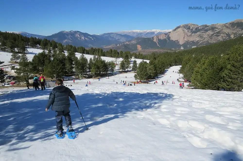 Niño en raquetas de nieve bajando por una ladera con muchas personas al fondo disfrutando de la nieve y tirándose en trineo, en Rasos de Peguera