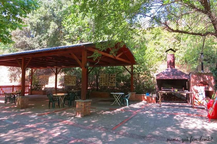 Porche con mesas y barbacoa en el Bar la Cabana del Llac de Navarcles