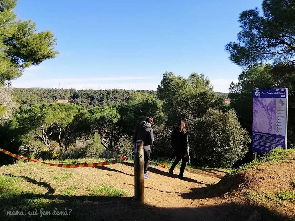 Dos personas accediendo al camino que lleva al Parc Fluvial del Ripoll por el barrio de Can Deu de Sabadell
