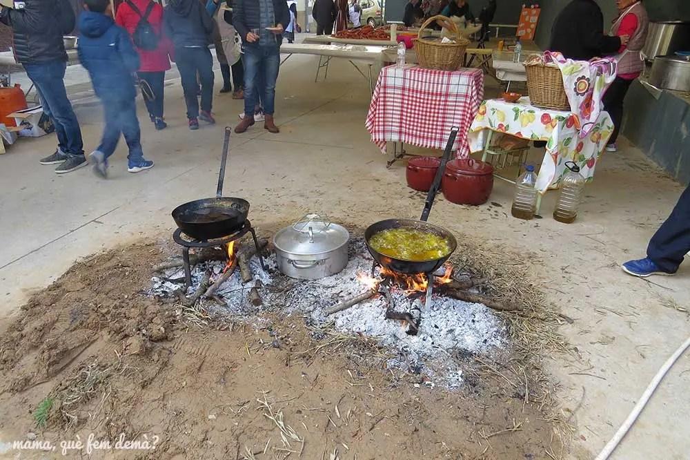 Ollas cociendo a fuego vivo en el suelo en la Fiesta de la Matacía de Colungo