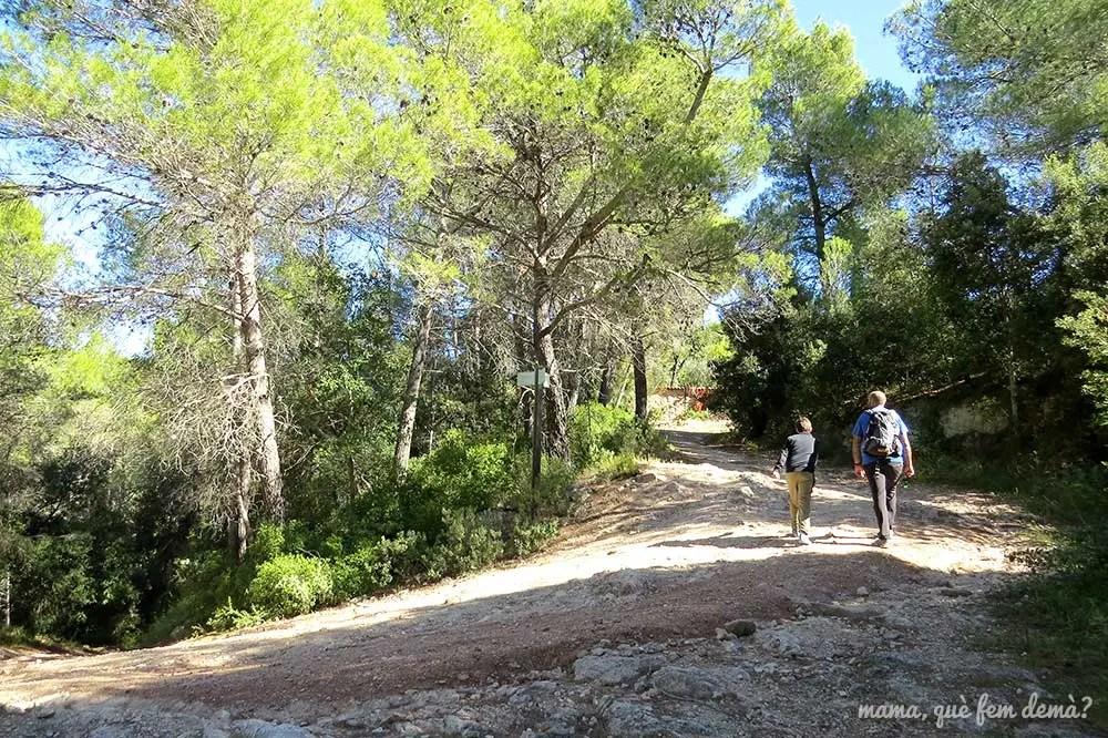 Dos personas caminando por el sendero de Can Rossell de les Bassegues que lleva al Santuari del Foix