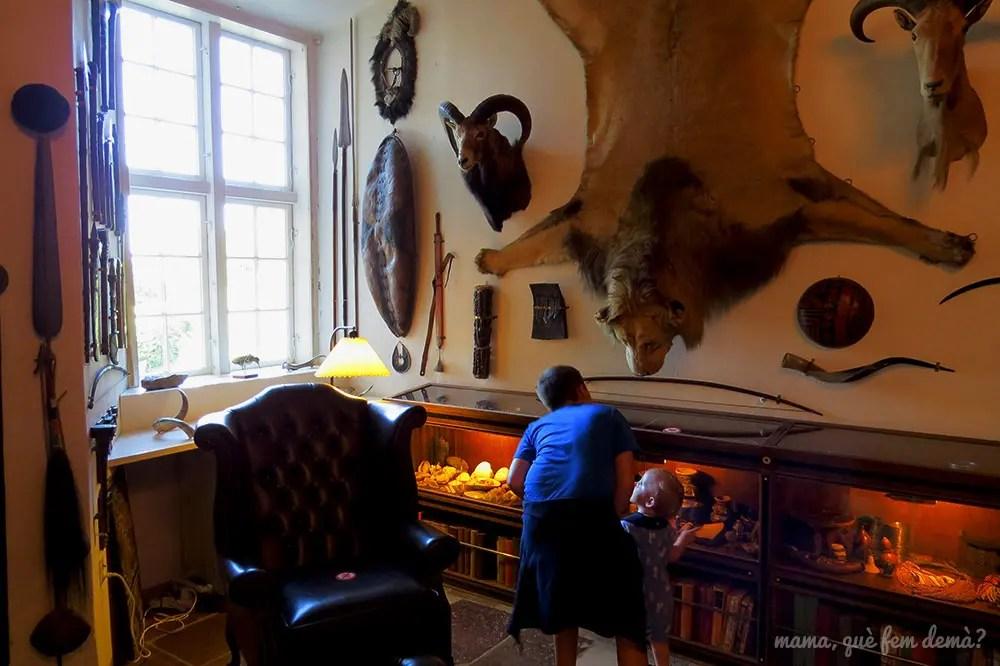 Interior de una de las salas de Castillo de Egeskov con trofeos de caza y una piel de león colgada de la pared y dos niños mirando