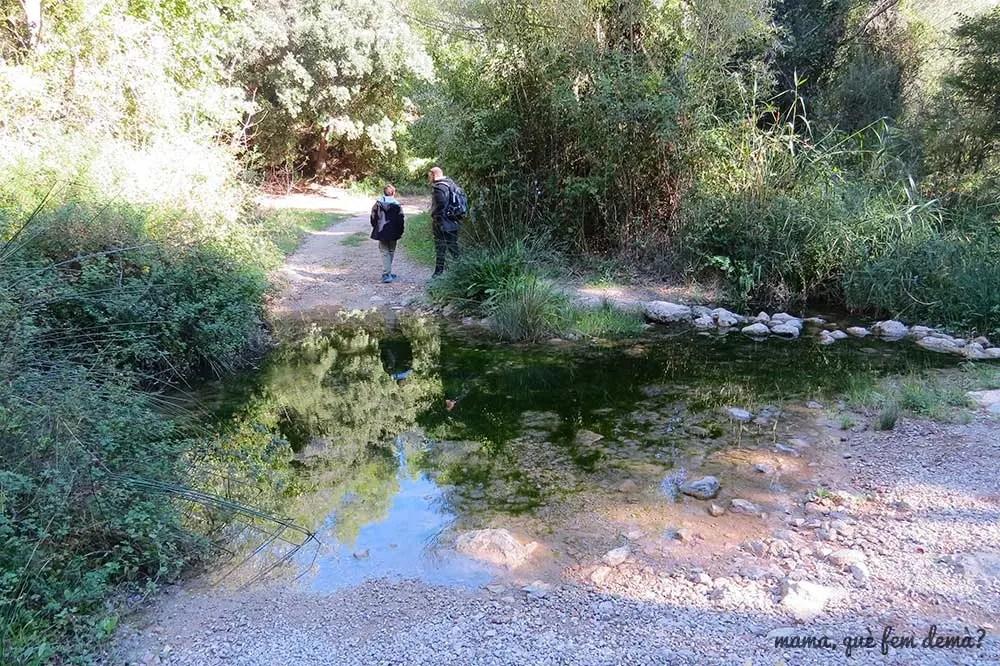 Dos personas cruzando el gual del trull en Torrelles de Foix