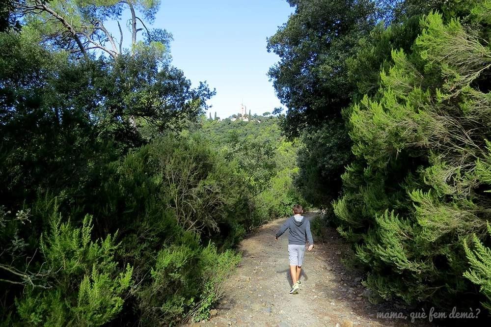 Niño caminando por la serra d'en Cardona con la casa Can potosí a lo lejos