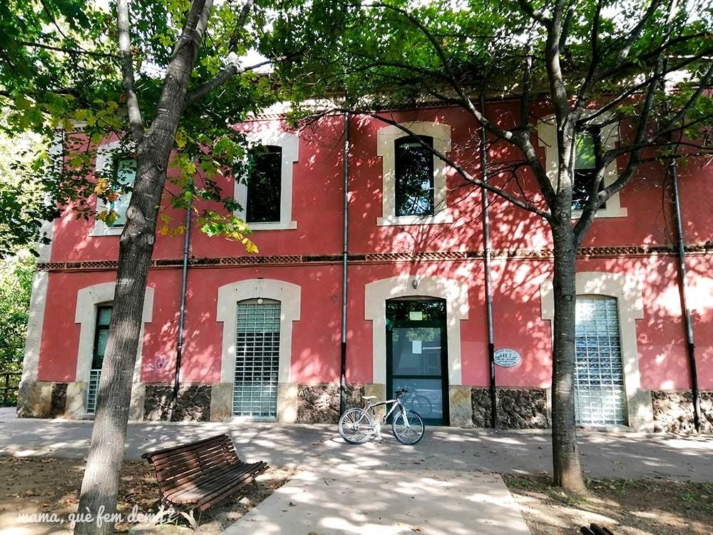 Exterior de la antigua estación de tren de Olot con una bicicleta apoyada en la fachada