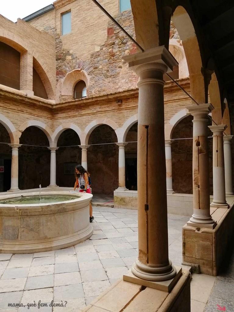 Mujer mirando la fuente central del claustro menor de la Cartoixa d'Escaladei