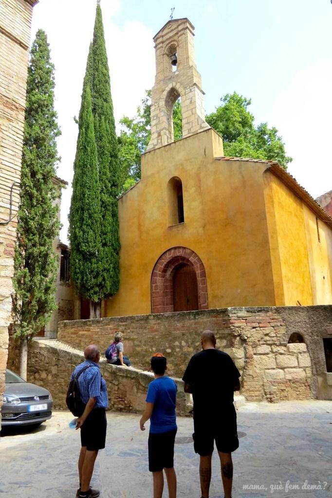 Personas mirando la fachada de la iglesia de la Mare de Déu de la Mercè en el pueblo de Escaladei