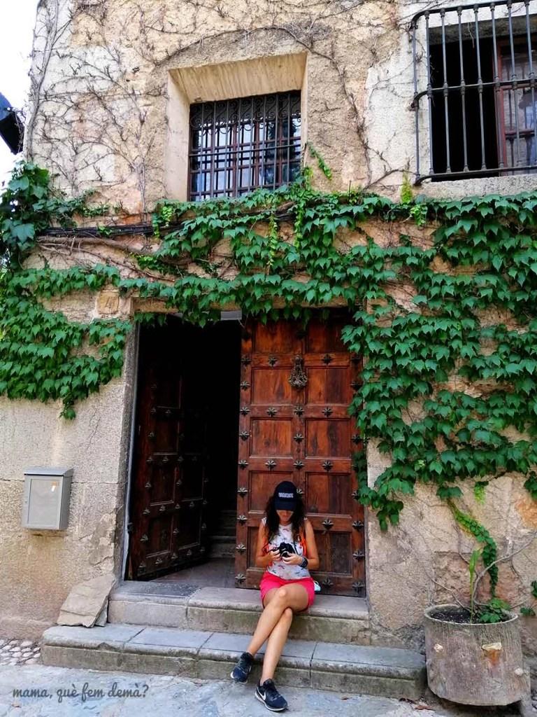 Mujer sentada en una puerta de una casa del pueblo de Escaladei