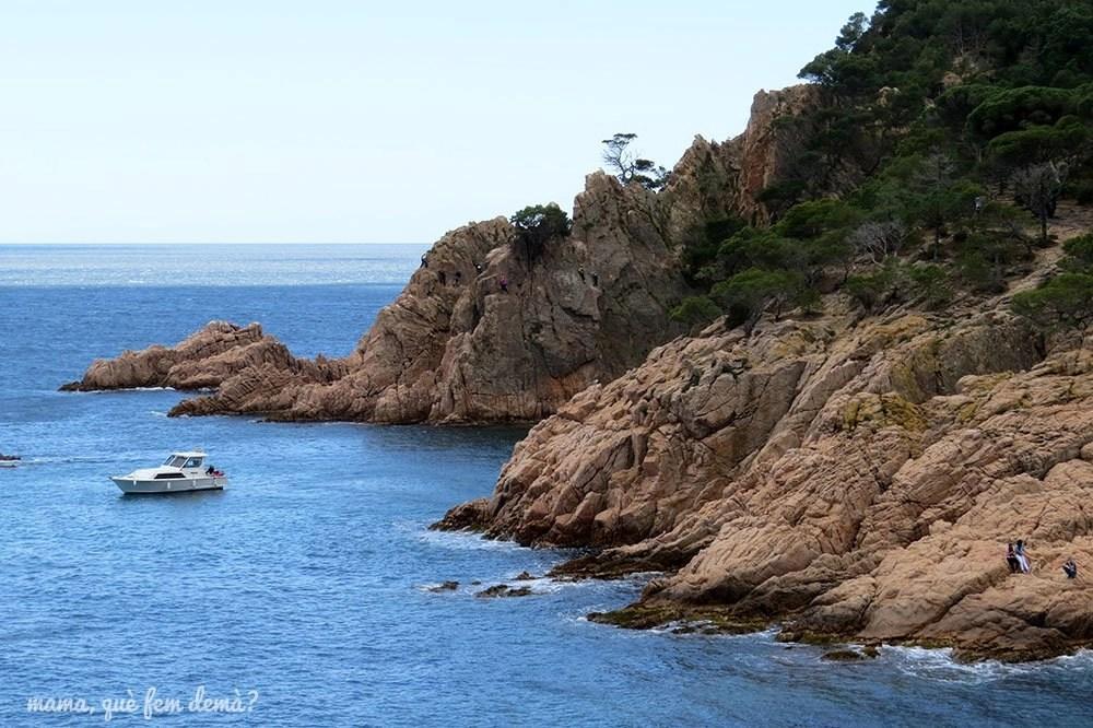 Barco navegando en una de las calas del camí de ronda de la platja de Sant Pol a Sant Feliu de Guíxols