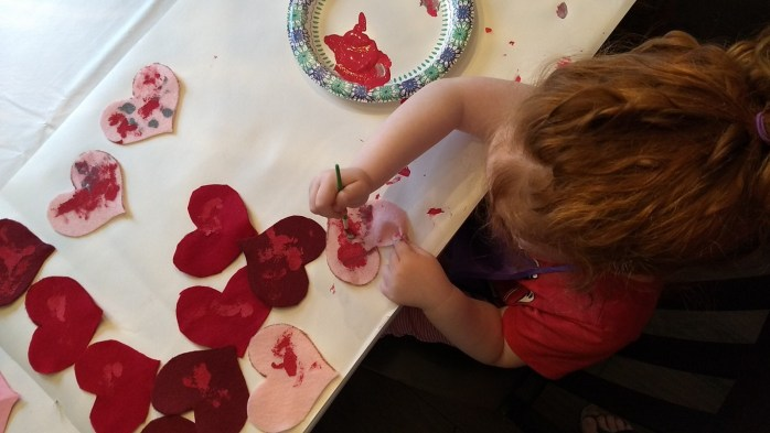 Girl paints felt hearts for making rice-filled handwarmers for Valentine's Day gifts, a project from Mama Rhythm Blog.