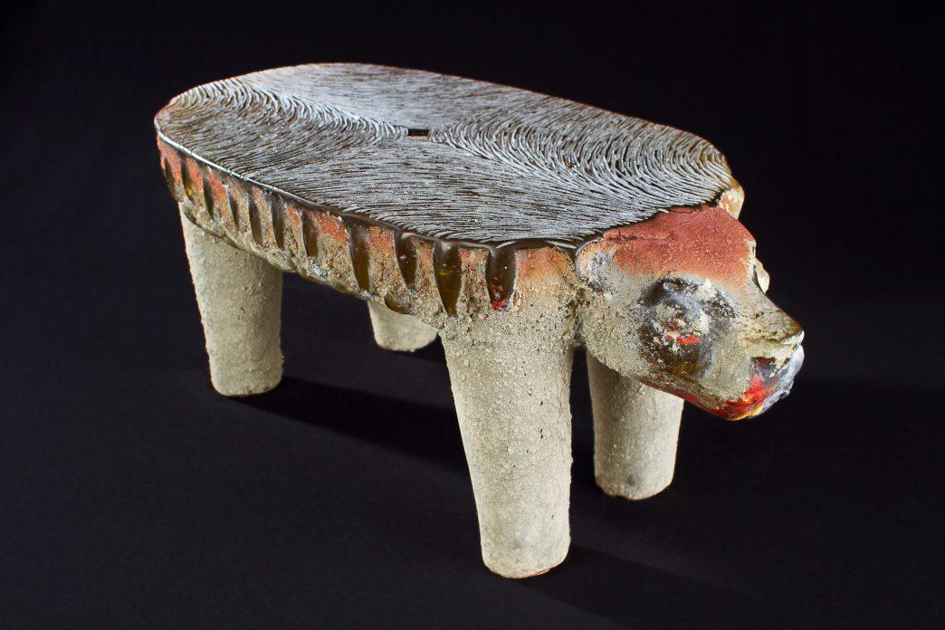 Glass sculpture of a jaguar shaped like a pre-Columbian metate
