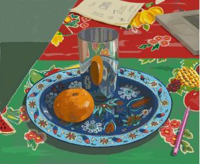 A blue painted plate containing an orange and a silver jar. The plate sits on a tabletop with a bright red patterned green and red tablecoth.