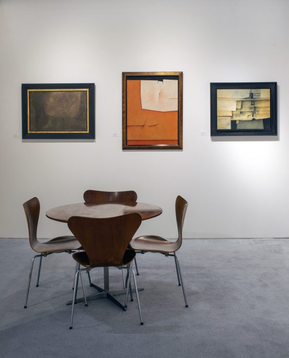 Installation shot of a booth at an art fair with three paintings