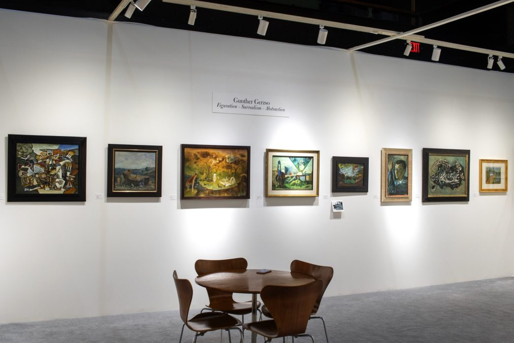 Installation shot of a booth at an art fair with paintings