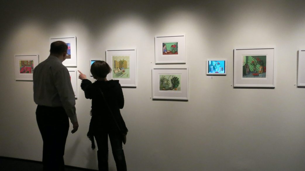 Installation shot of people viewing digital prints at the gallery