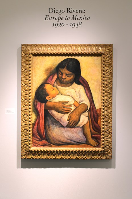 A peasant woman holds a sleeping child in her arms.