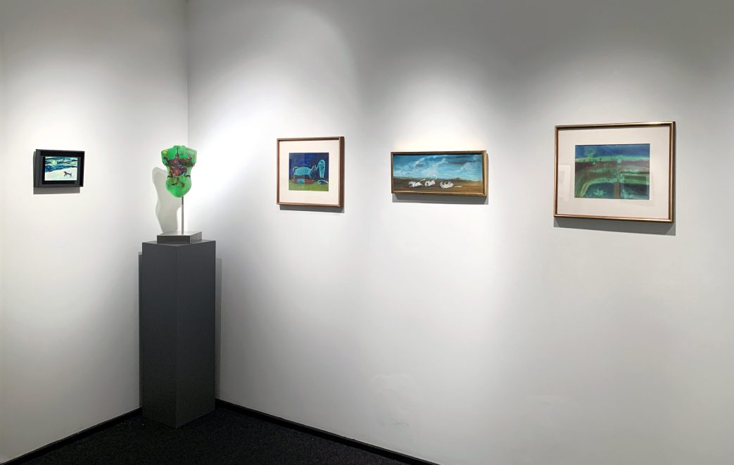 Installation shot of a wall of paintings and a glass sculpture in the front gallery