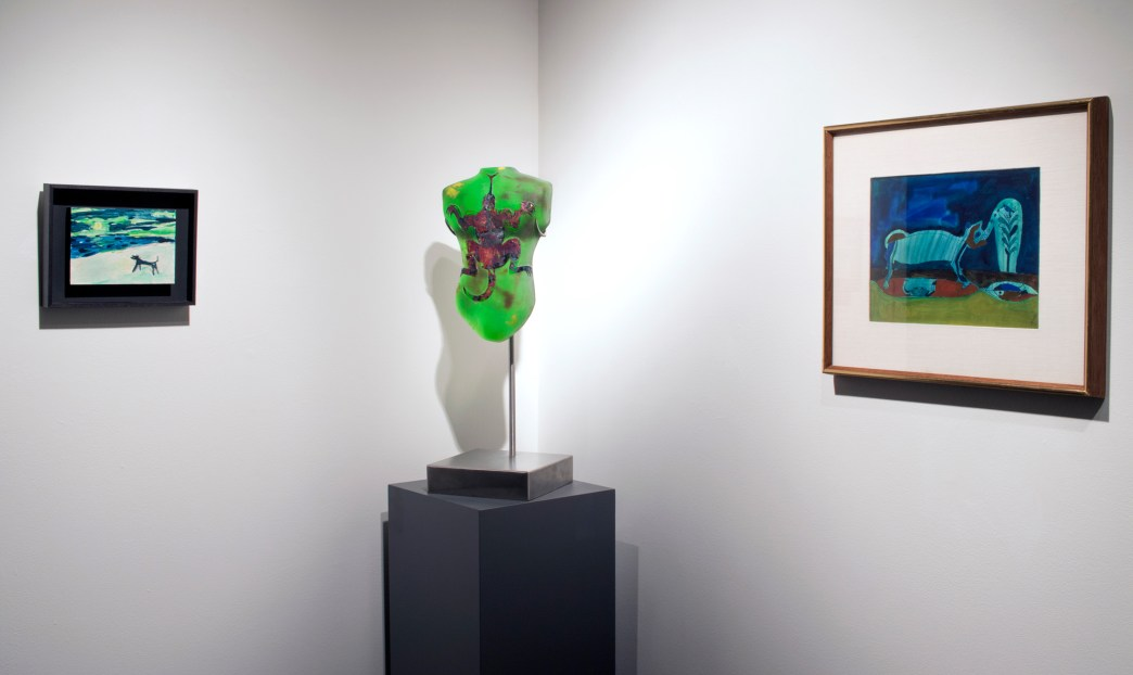 Installation shot of a green glass sculpture in between two paintings