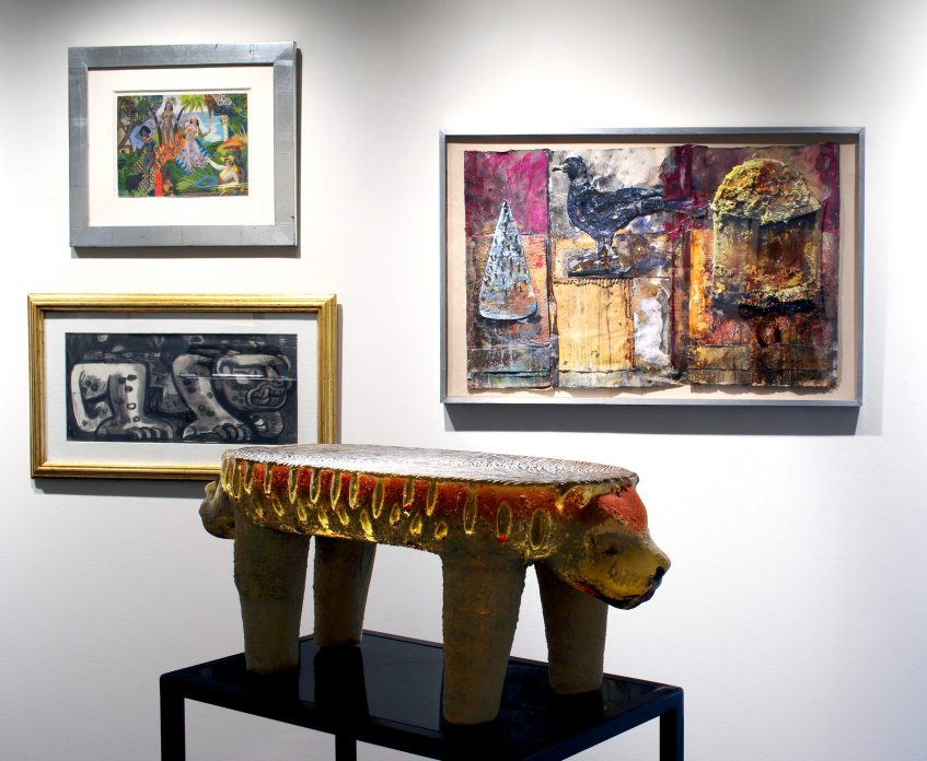 Picture of three artworks handing on the gallery wall and one small sculpture in front of them