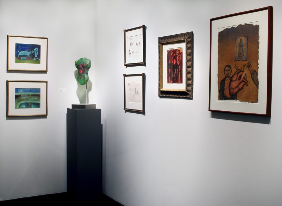 Picture of one corner of the gallery with a sculpture and six artworks hanging in the two corner walls