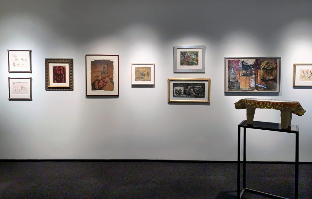 Picture of the gallery with 9 artworks on the wall and one sculpture in a stand